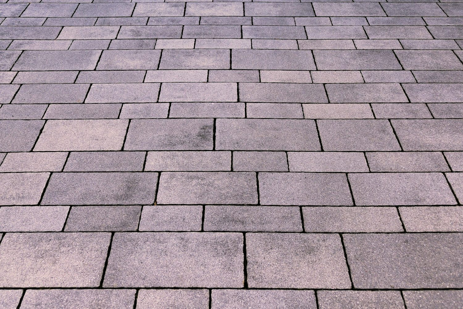 "A lot of people prefer utilizing paver stones to cover an outdoor area with a natural looking yet tough surface. The stones cover pathways, driveways, and porch areas. Furthermore, their little size makes them perfect for making curved edges and narrow borders. Most individuals hire someone to estimate the number of brick pavers that are required. But, the process is quite straightforward and you can do it as well. However, you must know the right size of the area to be covered along with the size of the brick pavers. Check out the below given points to estimate the brick pavers you will need. • Calculate The Total Project Area In Sq Ft: This estimation will help to determine the size of the area you wish to have paved. (length of the area in feet) x (width of the area in feet) = area in sq ft For instance: 5ft x 5ft = 25 sq ft On the off chance that the area where you want brick paves, has an irregular shape, then separate it into numerous segments. Calculate the region of every individual segment and add these together. • Deciding The Brick Paver Size: You may discover paver measurements are commonly listed as an ""estimation"". In order to determine the true size of the pavers, it is best to take your own measurements. Then to determine how many you will need, you will need to calculate the square footage of an individual paver. However, many pavers are marked in inches, not feet. *A square foot is equal to 144 square inches. (Length of brick paver in inches) x (Width of brick paver in inches) ÷ 144 = square footage per piece. For example: (7.7 in x 3.8 in) = 29.26 sq inches 29.26 q inches ÷ 144 square inches = 0.20 sq ft • Estimating How Many Pavers You Need: Now, you'll need to use the above two calculated values in order to decide what number of brick pavers your task requires. Once, you know the estimated number of brick paves you need, you are less likely to need to return to buy more pavers again and again. (area of the project in square feet) ÷ (square footage per piece) = estimated number of brick pavers. For example: The area you are paving is 25 sq ft and a single paver is 0.20 sq ft. 25sq ft ÷ 0.20 sq ft = 125 pavers *It is highly recommended to add 10 percent more brick pavers than you have estimated. The overabundance should account for breakage, pavers that you have to cut, and additional pavers to serve as replacements for any other repairs."