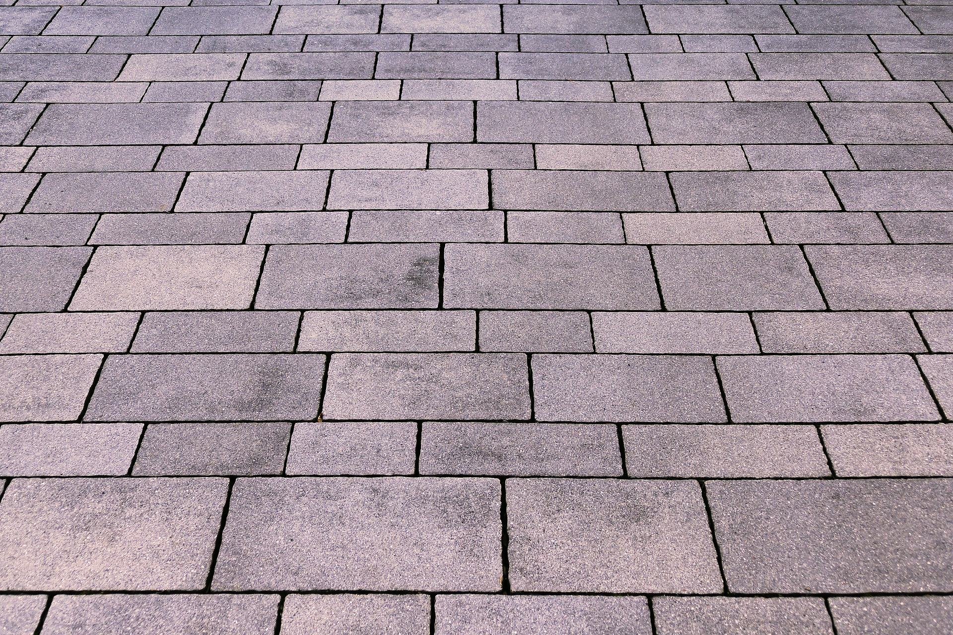 """A lot of people prefer utilizing paver stones to cover an outdoor area with a natural looking yet tough surface. The stones cover pathways, driveways, and porch areas. Furthermore, their little size makes them perfect for making curved edges and narrow borders. Most individuals hire someone to estimate the number of brick pavers that are required. But, the process is quite straightforward and you can do it as well. However, you must know the right size of the area to be covered along with the size of the brick pavers. Check out the below given points to estimate the brick pavers you will need. • Calculate The Total Project Area In Sq Ft: This estimation will help to determine the size of the area you wish to have paved. (length of the area in feet) x (width of the area in feet) = area in sq ft For instance: 5ft x 5ft = 25 sq ft On the off chance that the area where you want brick paves, has an irregular shape, then separate it into numerous segments. Calculate the region of every individual segment and add these together. • Deciding The Brick Paver Size: You may discover paver measurements are commonly listed as an """"estimation"""". In order to determine the true size of the pavers, it is best to take your own measurements. Then to determine how many you will need, you will need to calculate the square footage of an individual paver. However, many pavers are marked in inches, not feet. *A square foot is equal to 144 square inches. (Length of brick paver in inches) x (Width of brick paver in inches) ÷ 144 = square footage per piece. For example: (7.7 in x 3.8 in) = 29.26 sq inches 29.26 q inches ÷ 144 square inches = 0.20 sq ft • Estimating How Many Pavers You Need: Now, you'll need to use the above two calculated values in order to decide what number of brick pavers your task requires. Once, you know the estimated number of brick paves you need, you are less likely to need to return to buy more pavers again and again. (area of the project in square feet) ÷ (square foota"""